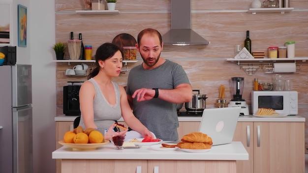 Ehemann beeilt sich bei der arbeit, während er beim frühstück einen bissen von geröstetem brot mit butter zu sich nimmt. gestresster mann, der sich spät beeilt, nervös schnell zum treffen eilt, zur arbeit eilt, zu spät zum termin