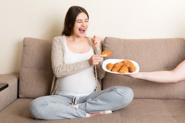 Ehemann bietet seiner schwangeren frau croissants an