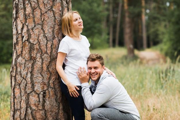 Ehemann, der auf schwangeren bauch der frau hört