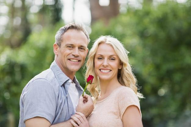 Ehemann, der draußen im wald eine rose frau anbietet