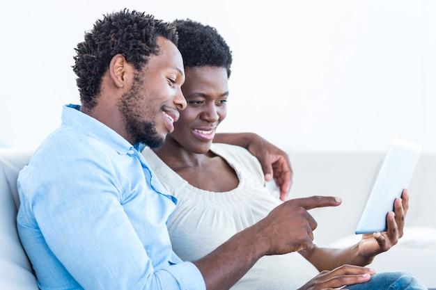 Ehemann, der in richtung zur digitalen tablette beim sitzen mit frau auf sofa zeigt
