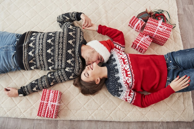 Ehemann, der seine frau küsst. draufsicht des paares in weihnachtskleidung liegt auf dem boden mit geschenken darauf.
