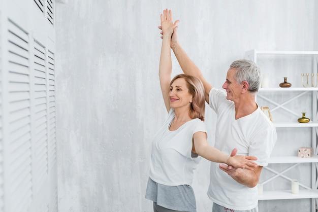 Ehemann, der seine frau unterstützt, wenn er yogaübung tut