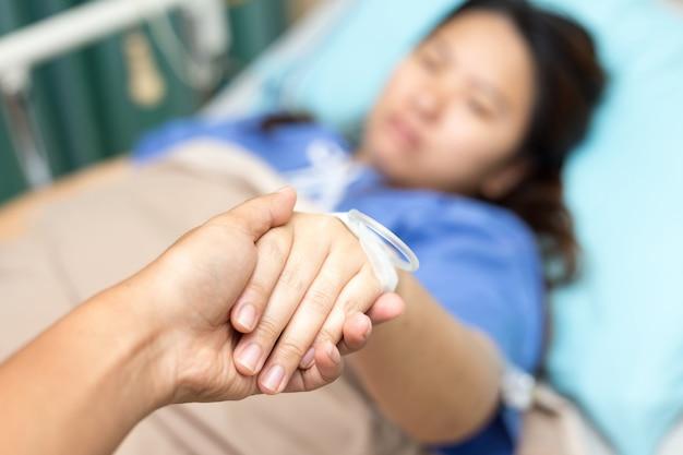 Ehemann, der seine geduldige hand asien in patien raum hält