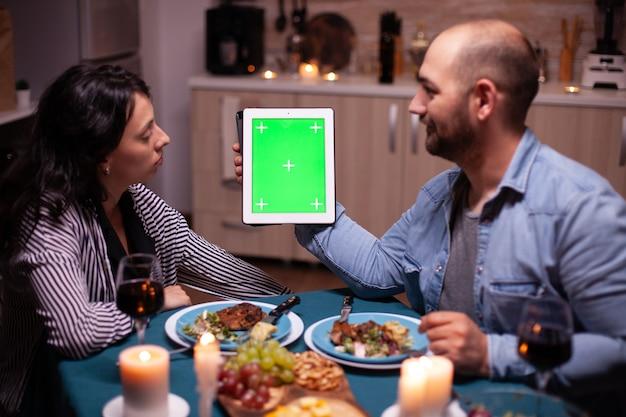 Ehemann, der tablet mit grünem bildschirm hält und frau beim romantischen abendessen ansieht.
