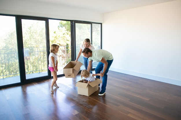 Ehemann, ehefrau und ihre töchter spielen mit kisten und ziehen in ein neues zuhause