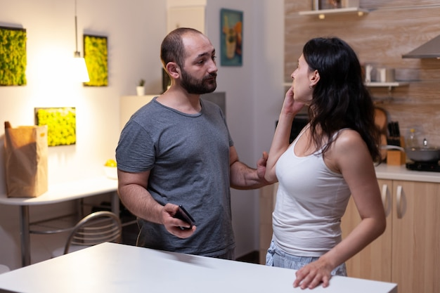 Ehemann hält smartphone von ehefrau mit geheimen nachrichten, die wegen eifersucht und untreue streiten. gereizte frau mit liebhaber wurde zu hause beim betrug mit technologie und chat-text erwischt