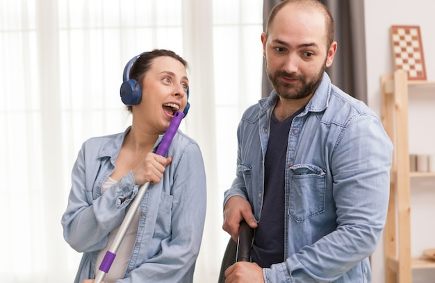 Ehemann ignoriert seine frau, während er versucht, den boden mit einem staubsauger zu reinigen
