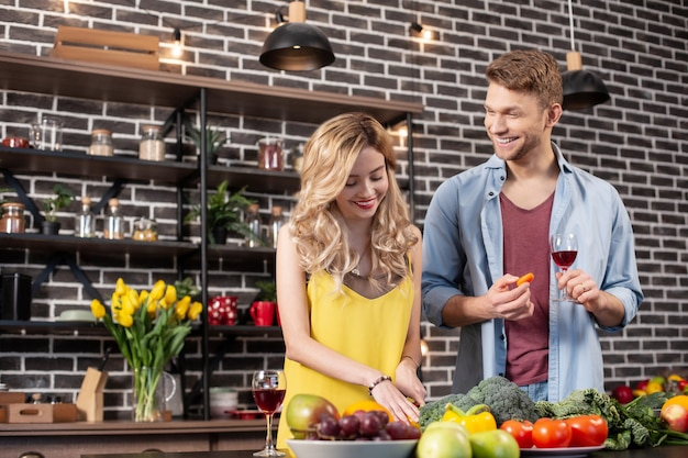 Ehemann lächelt. glücklicher strahlender bärtiger ehemann, der breit lächelt und seiner frau beim kochen des abendessens zusieht?