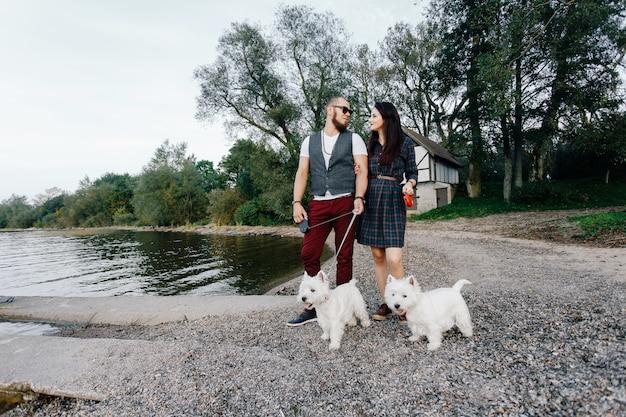 Ehemann mit einer schönen frau, die ihre weißen hunde im park geht