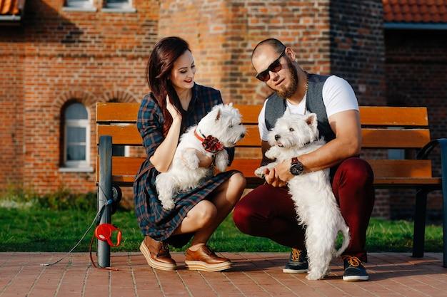 Ehemann mit einer schönen frau, die ihre weißen hunde in der straße geht