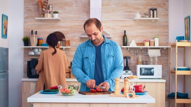 Ehemann schneidet tomaten beim zubereiten von salat mit frau in der küche. gesundes gemüse kochen, das gesundes bio-lebensmittel glücklich zusammen lebensstil zubereitet. fröhliches essen in der familie mit gemüse