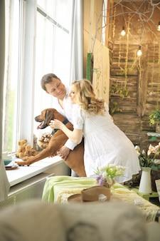 Ehemann, schwangere frau und ein hund, der in ein großes fenster schaut