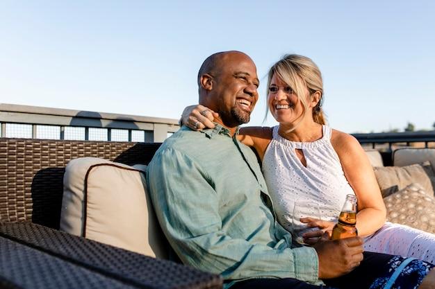 Ehemann und ehefrau entspannen sich auf ihrem dach während der sperrung von covid-19