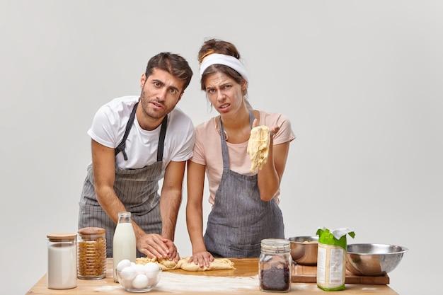 Ehemann und ehefrau posieren in der küche und bereiten ein leckeres abendessen vor