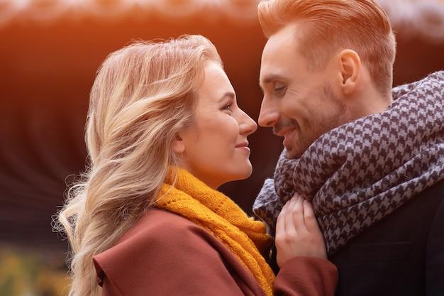 Ehemann und ehefrau umarmten sich lächelnd und sahen sich im herbstpark an