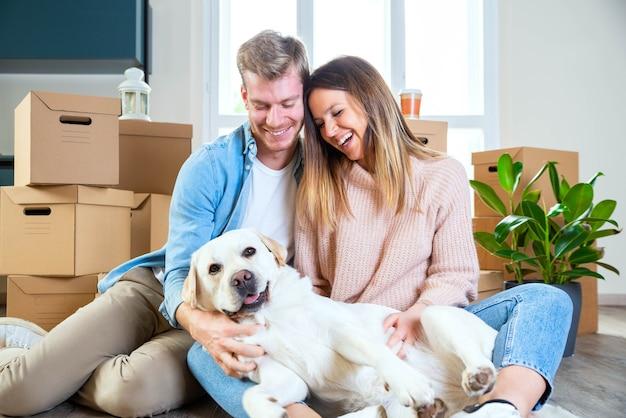 Ehemann und ehefrau und ihr hund ziehen in ein neues zuhause