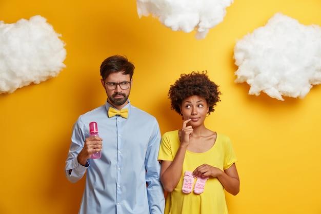 Ehemann und ehefrau warten auf das baby, posieren mit der flasche und den neugeborenen stiefeln, überlegen sich den namen des zukünftigen kindes, machen sich bereit, eltern zu werden, isoliert auf gelben, weißen wolken über ihnen