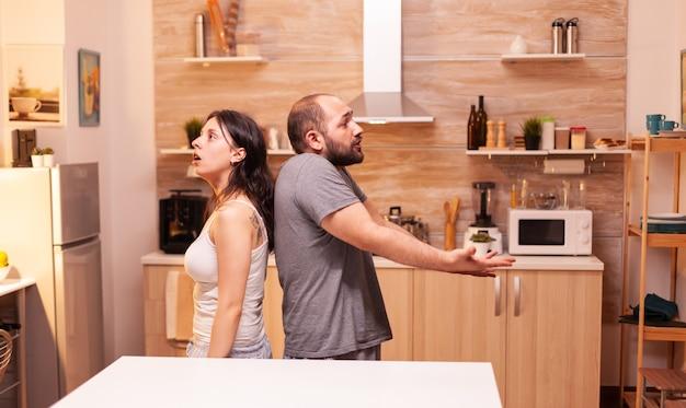 Ehemann verärgert über betrügerische frau, die rücken an rücken mit einer meinungsverschiedenheit bleibt. frustriert beleidigt irritiert beschuldigt frau der untreue, die sie beschuldigt.