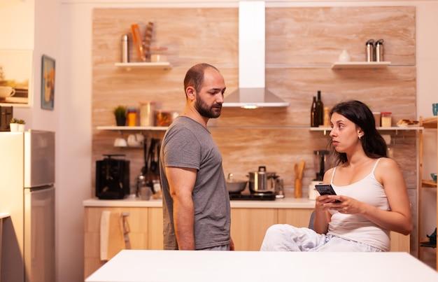 Ehemann verdächtigt seine frau, mit einem anderen mann betrogen zu haben, während sie eine sms schreibt. frustriert beleidigt irritiert beschuldigt frau der untreue, die sie beschuldigt.