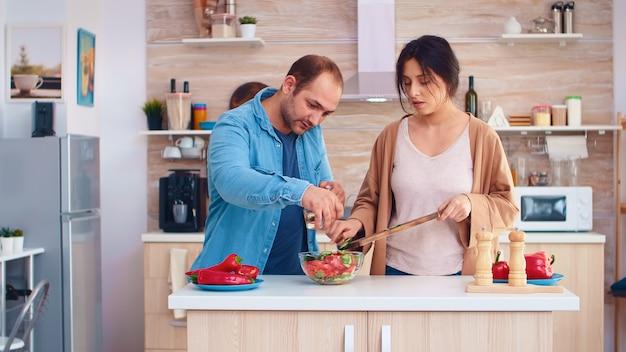Ehepaar bereitet salat mit frischem gemüse in der küche zu. kochen, das gesundes bio-lebensmittel glücklich zusammen lebensstil zubereitet. fröhliches essen in der familie mit gemüse