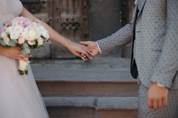 Ehepaar, das hände hält und brautstrauß trägt. braut- und bräutigamkonzept