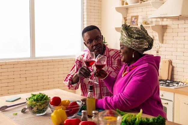 Ehepaar. erfreutes positives paar, das lächelt, während es das mittagessen für sich selbst kocht