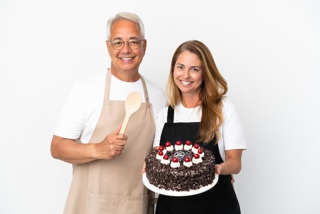 Ehepaar koch mittleren alters hält geburtstagstorte isoliert auf weißem hintergrund