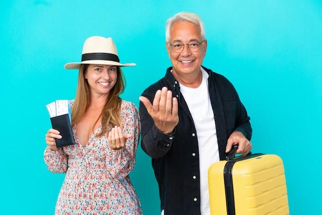 Ehepaar mittleren alters, das auf reisen geht und einen koffer auf blauem hintergrund isoliert hält, der einlädt, mit der hand zu kommen. schön, dass du gekommen bist