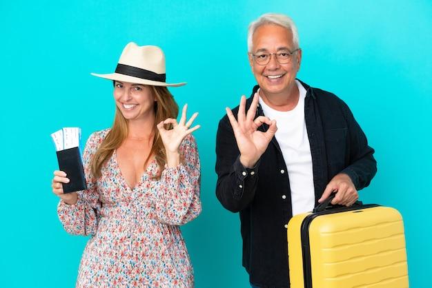 Ehepaar mittleren alters, das auf reisen geht und einen koffer hält, der auf blauem hintergrund isoliert ist und ein ok-zeichen mit den fingern zeigt