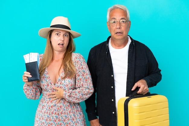 Ehepaar mittleren alters, das auf reisen geht und einen koffer hält, der auf blauem hintergrund mit überraschung und schockiertem gesichtsausdruck isoliert ist?