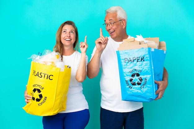 Ehepaar mittleren alters, das eine recyclingtüte voller papier und kunststoff hält, die auf weißem hintergrund isoliert ist, um die lösung zu realisieren, während es einen finger hochhebt