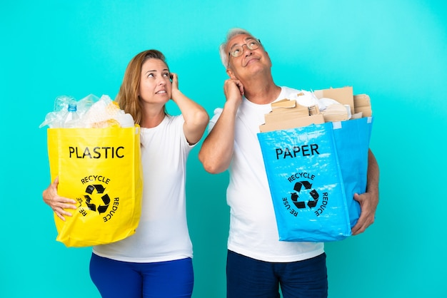 Ehepaar mittleren alters, das eine recyclingtüte voller papier und kunststoff hält, die auf weißem hintergrund isoliert ist und eine idee denkt, während es sich am kopf kratzt?
