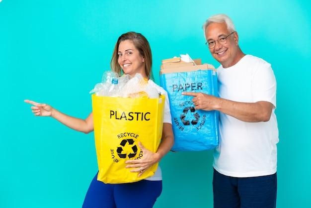 Ehepaar mittleren alters, das eine recyclingtüte voller papier und kunststoff hält, isoliert auf weißem hintergrund und zeigt mit dem finger zur seite in seitlicher position
