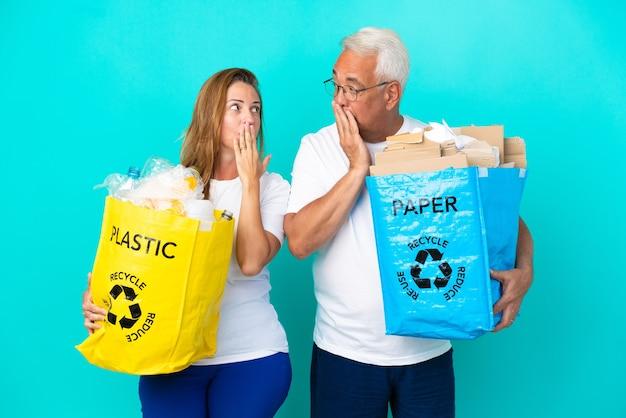 Ehepaar mittleren alters, das einen recyclingbeutel voller papier und plastik hält, isoliert auf weißem hintergrund, der den mund mit den händen bedeckt, um etwas unangemessenes zu sagen?