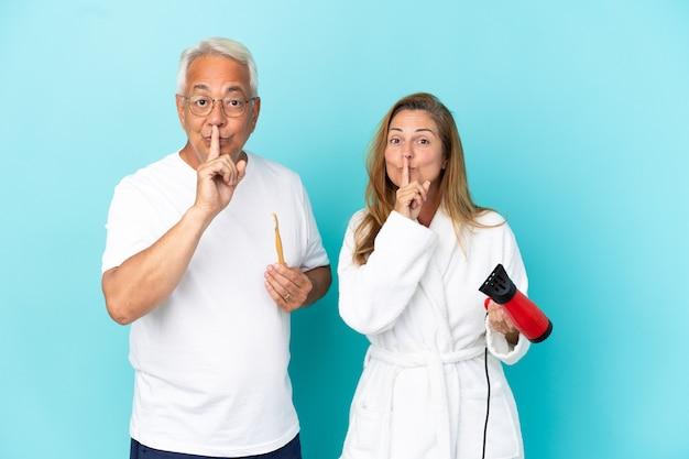 Ehepaar mittleren alters, das trockner und zahnbürste einzeln auf blauem hintergrund hält und ein zeichen der stille zeigt, die den finger in den mund steckt