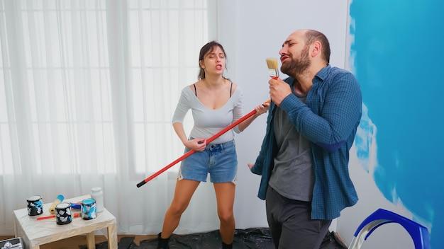 Ehepaar singt auf renovierungswerkzeugen, die in blaue farbe getaucht sind. fröhliches ehepaar während der hausverjüngungskur. heimtextilien und renovierung in gemütlicher wohnung, reparatur und verjüngungskur