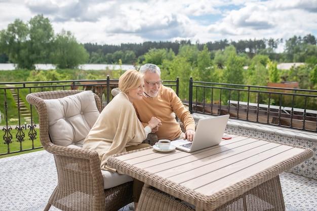 Ehepaar sitzt auf der terrasse und surft zusammen im internet