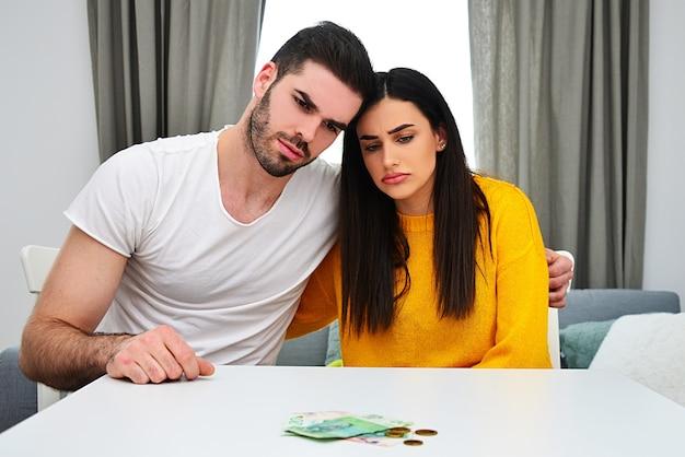 Eheprobleme, geldprobleme, verantwortungsbewusster umgang mit geld, sparkonzept. junges paar, das geld auf dem tisch betrachtet und besorgt aussieht.