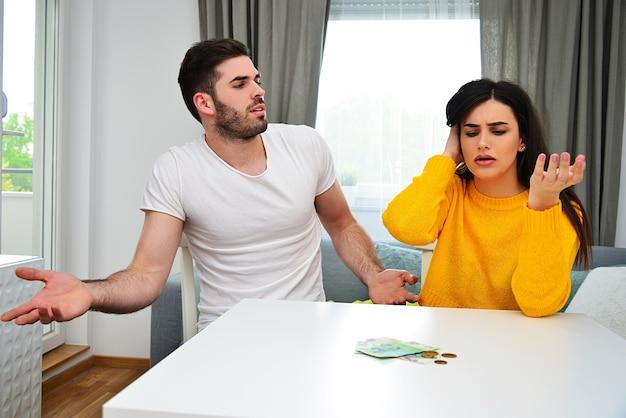 Eheprobleme, geldprobleme, verantwortungsbewusster umgang mit geld, sparkonzept. junges paar, das geld auf dem tisch betrachtet und sich besorgt sieht.