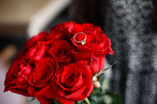 Ehering am finger des mädchens. strauß roter rosen. verlobungsgeschenk.