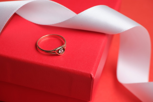 Ehering auf einer roten geschenkbox und einem weißen band.