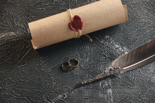 Eheringe auf der figur eines gebrochenen herzens von einem baum, hammer eines richters auf einem hölzernen hintergrund. scheidung scheidungsverfahren
