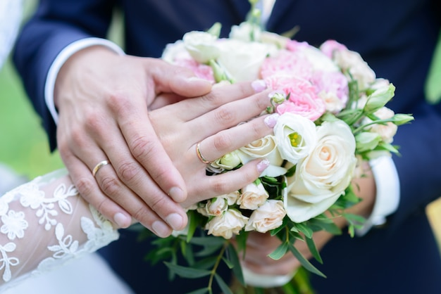 Eheringe auf einem kissen ein strauß pfingstrosen, die hände mit ringen heiraten