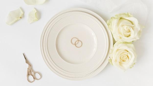 Eheringe auf keramischer platte mit rosen und schere auf weißem hintergrund