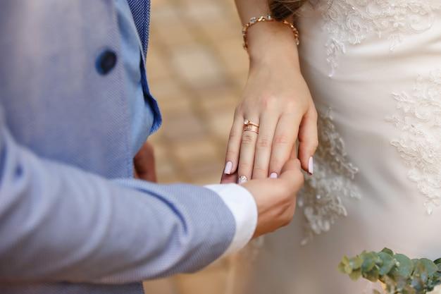 Eheringe. bräutigam, der hand der braut auf hochzeitszeremonie hält.