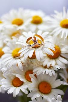 Eheringe bräutigam und braut, die auf blumen liegen