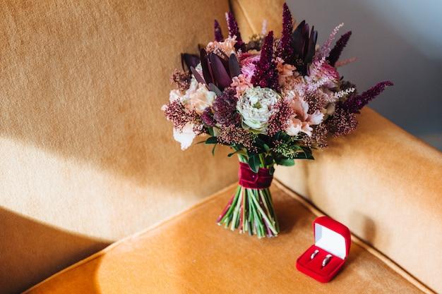 Eheringe und bouquete auf sessel. blumenstrauß mit verschiedenen schönen blumen