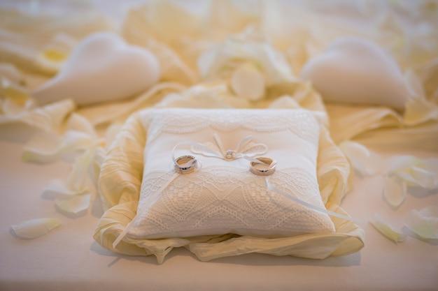 Eheringe zusammen mit weißem seil auf weißem kissen mit weißen herzen herum. hochzeitszeremonie