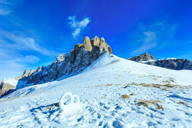 Eheringskulptur aus dem schnee am winterberghang (sella pass, italien).